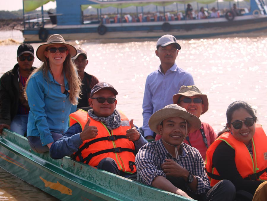 Elizabeth Everest dons a sun hat while on a boat in Cambodia with local Wonders of the Mekong team members.