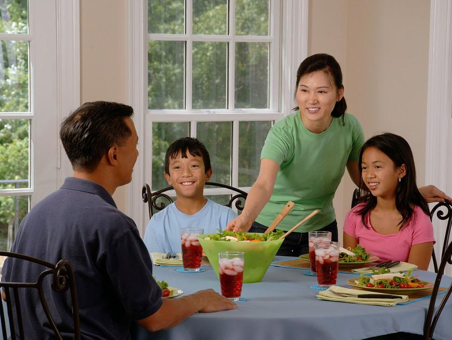 Asian family of four eating dinner at a table