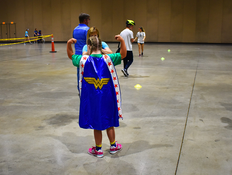 Young women pointing to a cape facing away from the camera