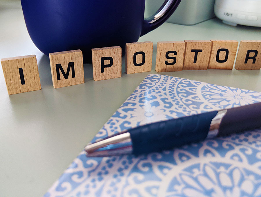"Pen and block letters spelling ""impostor"" on a table"