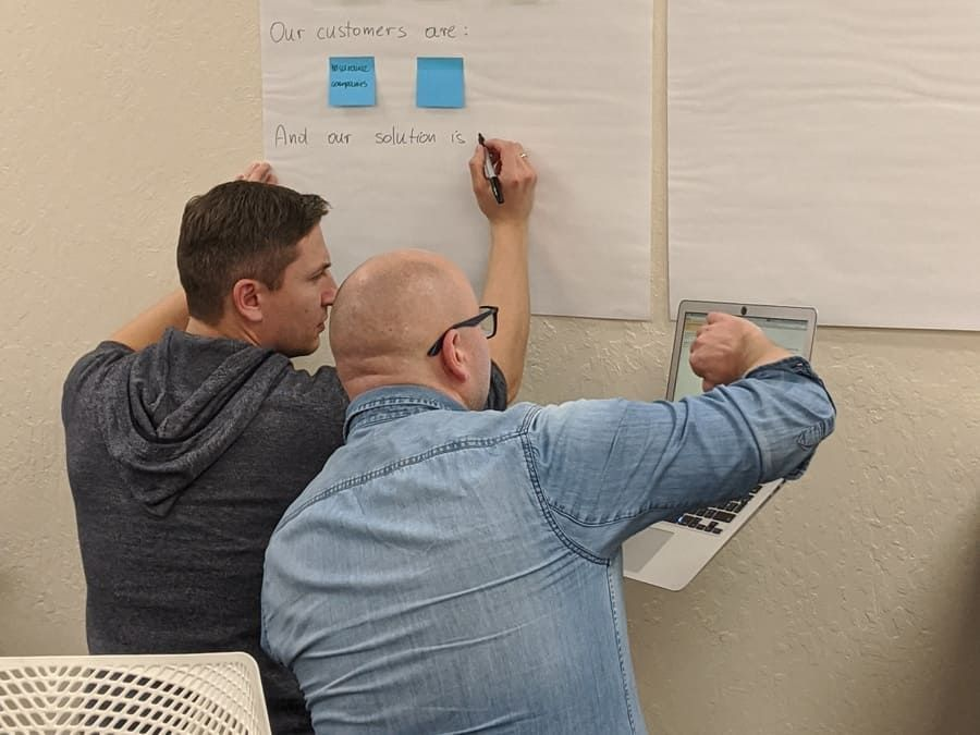 Two workshop participants developing content on flipchart paper