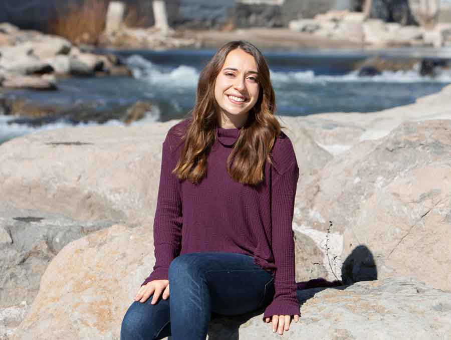 Lauren Mazurowski sits on some rocks by the river.