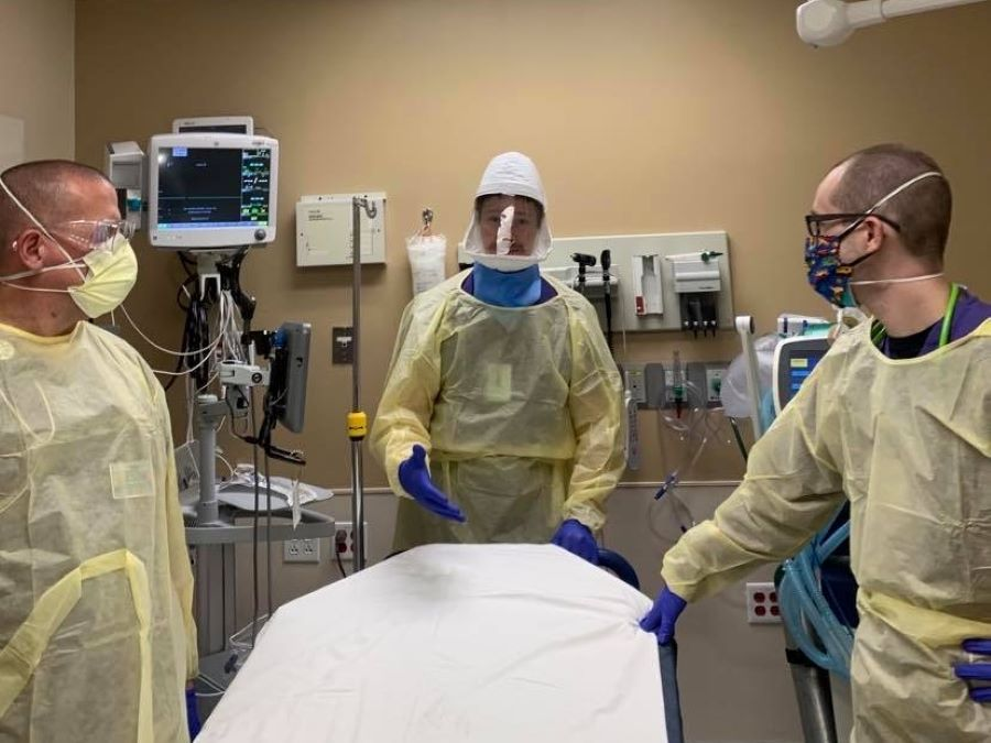 Three healthcare workers wearing protective gear including masks, shields and gowns, in a procedure room.