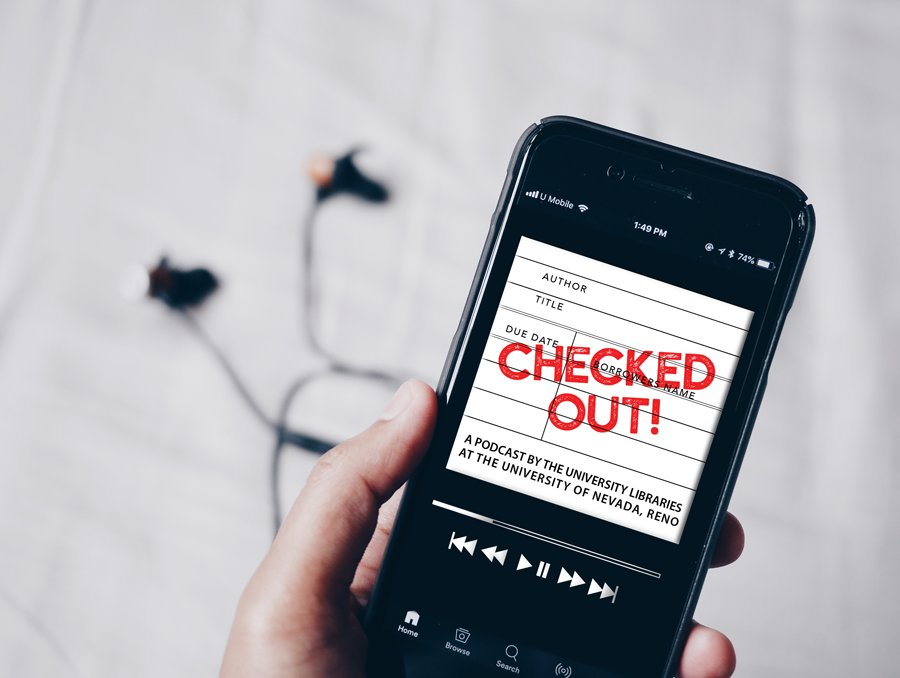 "Unidentified person holds a smartphone with headphones in the background. On the screen of the smartphone is an image of the ""Checked Out!"" podcast art. It features a white background and looks like an old fashioned library check out card. There is a red stamp across the image that says ""Checked Out!"" ""Checked Out!"" is a podcast by the University Libraries at the University of Nevada, Reno."