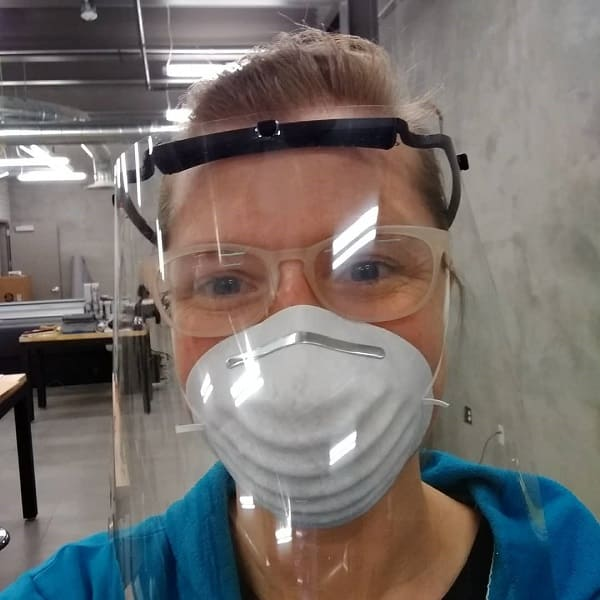 Nicole Miller models a face shield 3D printed in the Art Department Fabrication Lab.