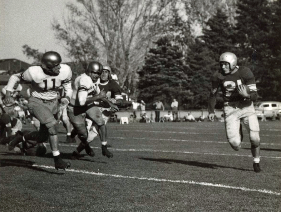 Black and white image of men in football uniform chasing another player holding the ball.
