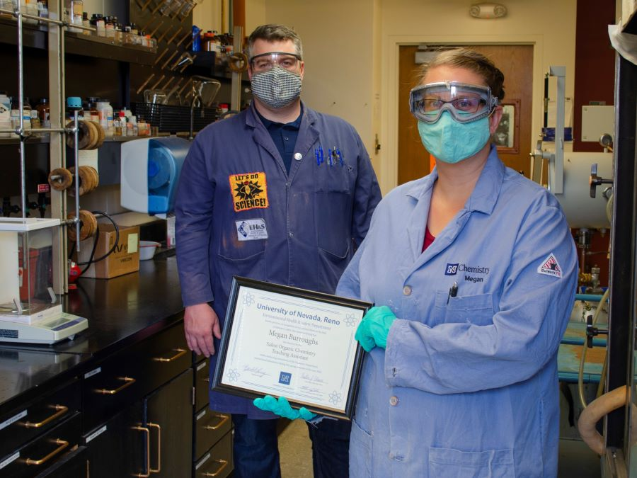 Laboratory training manager presents a certificate to teaching assistant in the lab, while both wear Personal Protective Equipment