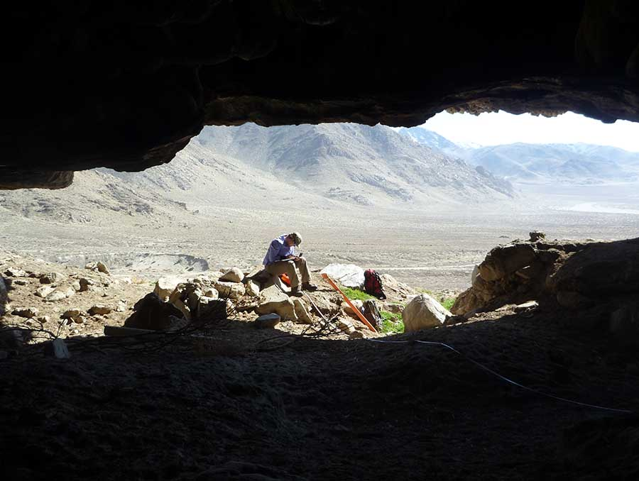 A man sits in the opening of a cave overlooking the Nevada dessert
