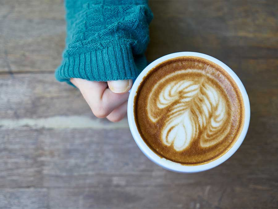 A hand holds a full coffee mug by the handle above a wooden table