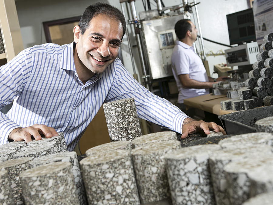 Elie Hajj inspects asphalt samples and smiles at camera
