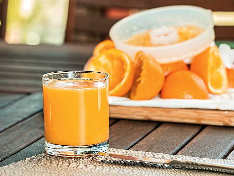A glass of fresh-squeezed orange juice on a table next to fresh orange slices