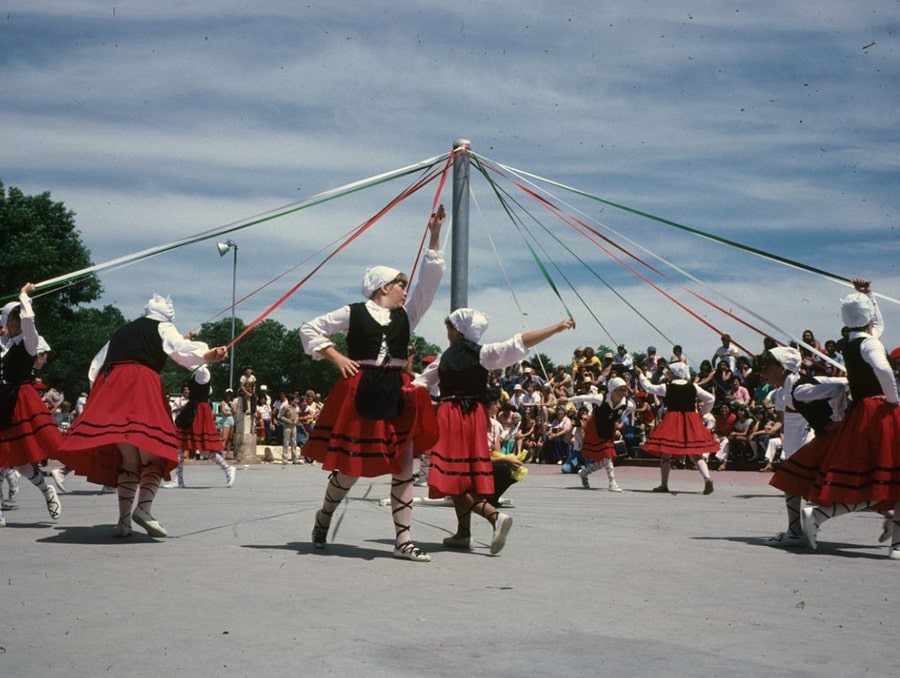 : A group of dancers participating in what appears to be a version of the Zinta Dantza, a ribbon dance. The colored ribbons are braided with the movement of the dancers around the pole. Metaphorically, the dance represents the process of life, the obstacles encountered as life progresses, and the passing from life to the afterlife.