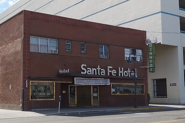 "Single-story red brick building with ""Santa Fe Hotel"" neon signage on the exterior."