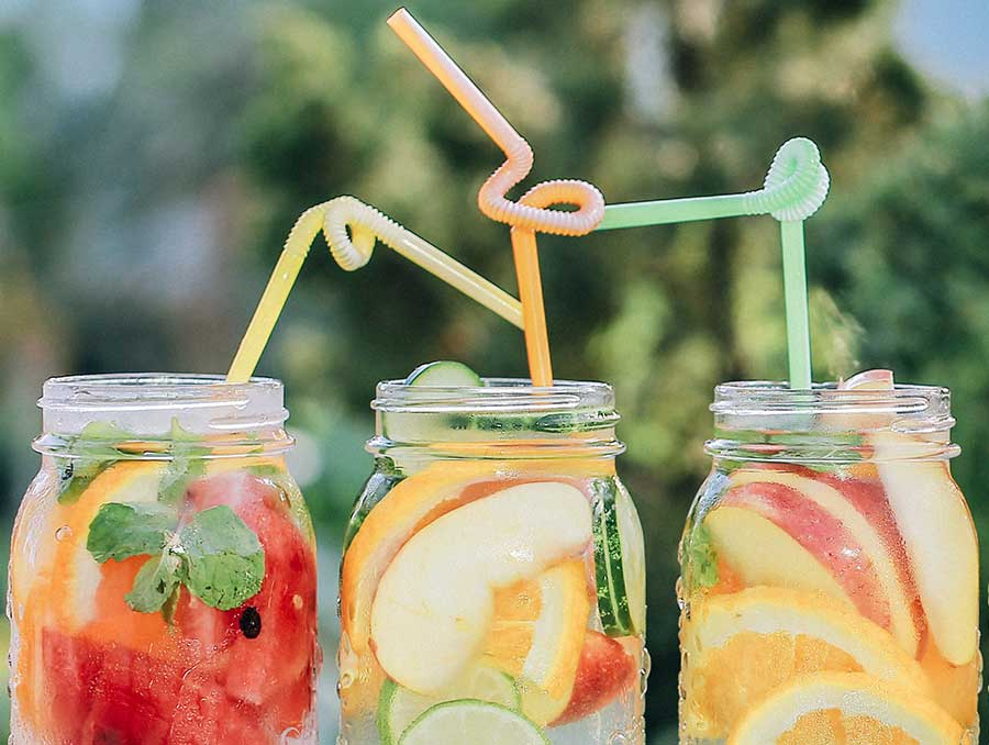 Three sugary fruity drinks in canning jars, each with a colorful bendy straw