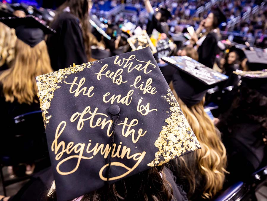 """Black mortar board graduation cap that reads in gold lettering, """"What feels like the end is often the beginning"""""""