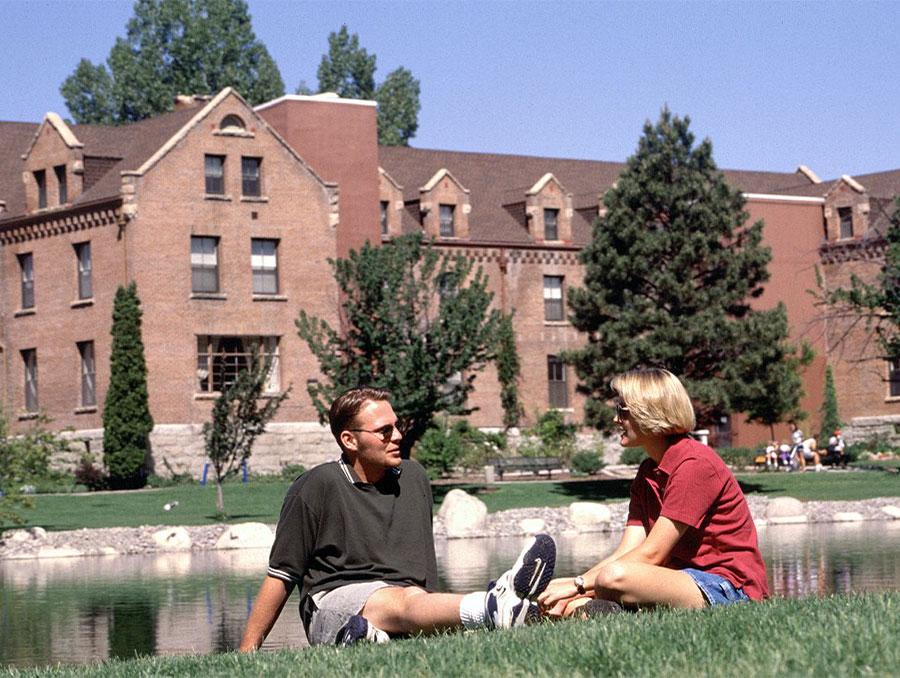 Two students shit close together talking in front of Manzanita Hall and Manzanita Lake, 2000