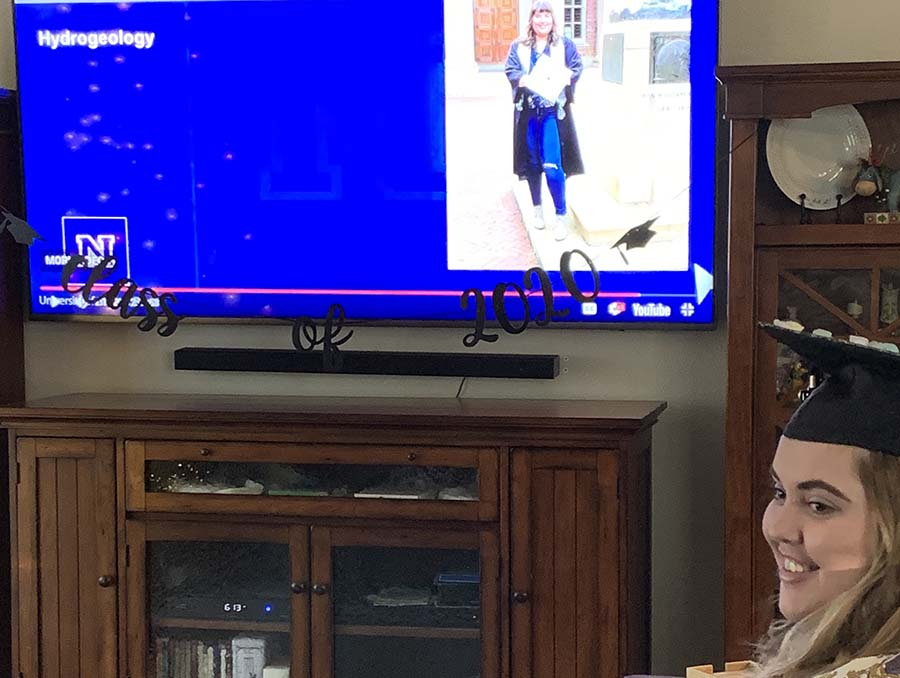 Student sits in living room with a cap and gown on with the University of Nevada, Reno commencement program on the television.