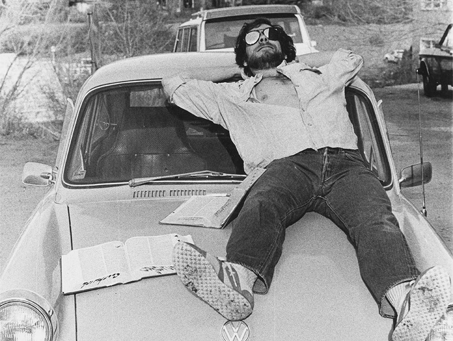 Black and white  photograph of a man wearing sunglasses and laying on top of a white car, 1979