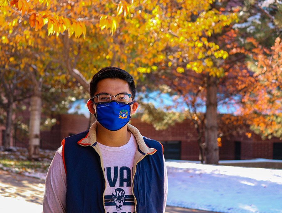 Student standing in front of trees with fall leaves and they have a mask on