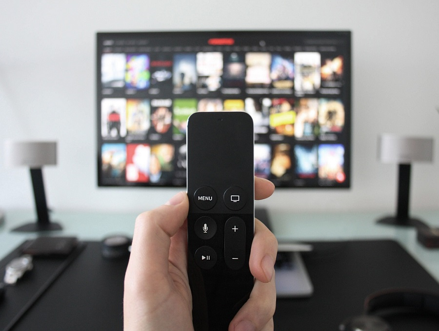 Person pointing a TV remote at a television screen with different TV programs.