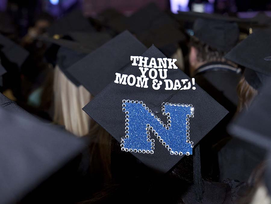 "A black graduation cap with the words ""Thank you Mom & Dad!"" on the mortar board."