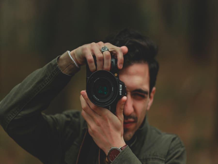 Ben Engel holds a camera up and looks through it in front of a blurred greenery background.