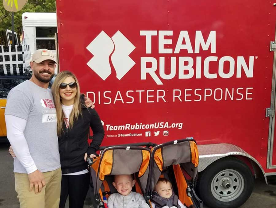 Austin Pollard in front of the Team Rubicon truck when volunteering for North Carolina the disaster relief program