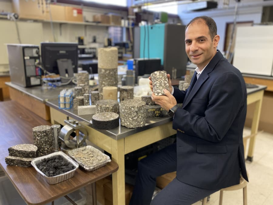 University Civil and Environment Engineering Professor Elie Y. Hajj sits at a workable in a pavement lab, holding an asphalt sample.