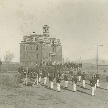 An old, black and white photo of Morrill Hall from 1901 with a uniformed cadet corps in front of it