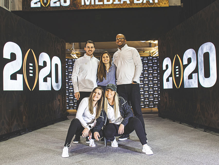 Five university alumni pose in front of a stadium tunnel at the College Football Playoff.