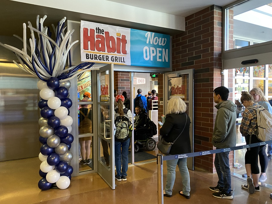 "The line at the opening of Habit Burger Grill. Students are inside the location and entering under a ""the Habit Burger Grill - Now open!"" sign and a silver and blue balloon palm tree."