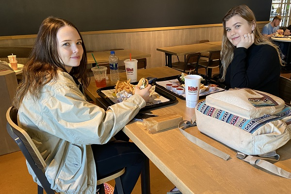 Two students sit at a table at the Habit Burger Grill with food