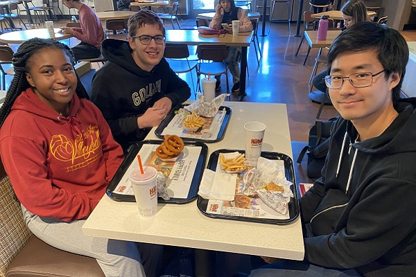 A trio of students sit together at the Habit Burger Grill with their food