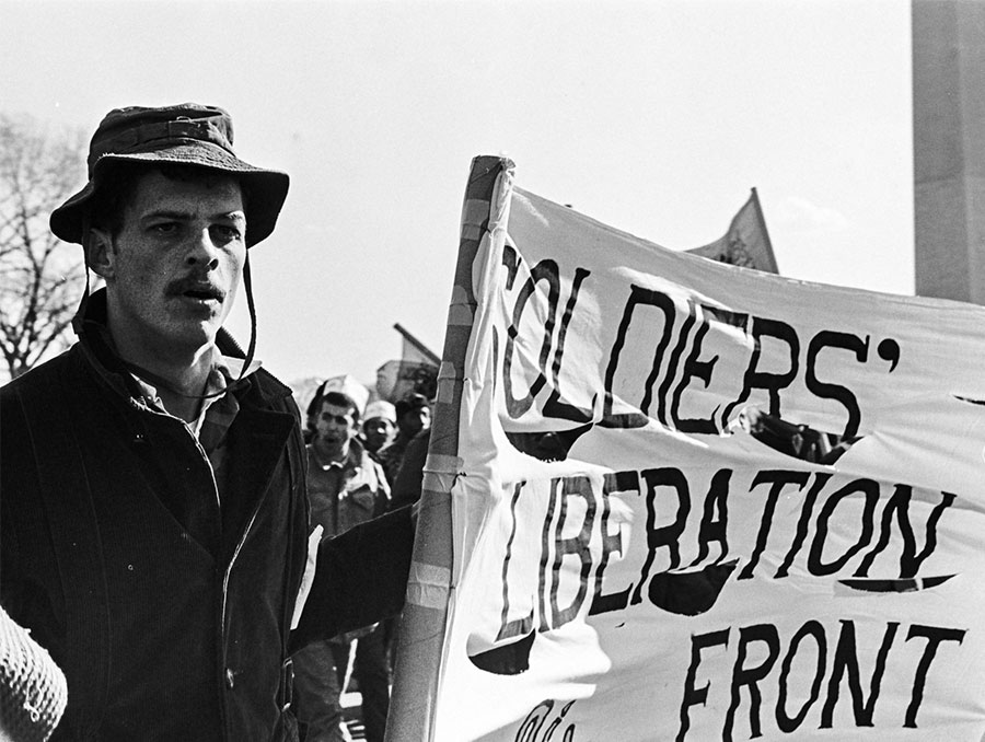 "Man holds sign that reads ""soldiers' liberation front"""