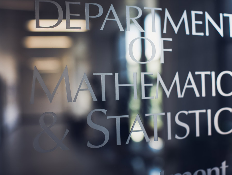 "Image of a glass door with ""Department of Mathematics and Statistics"" etched on it."