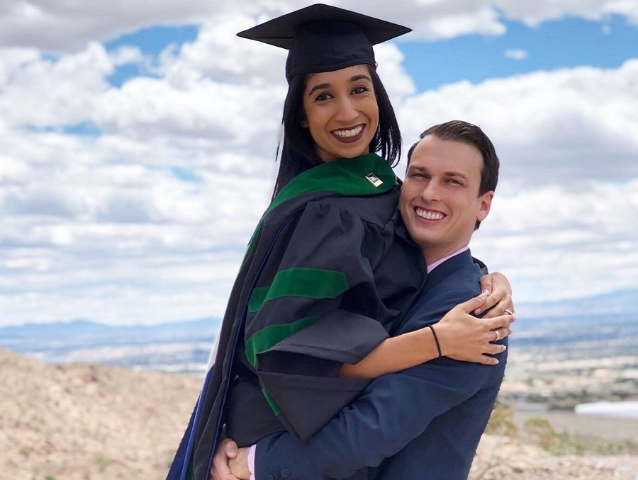 Aradhana Mehta and Lance Horner posing for a cute photo in which Aradhana is being held up in her medical school graduation attire by Lance, who is in a suit