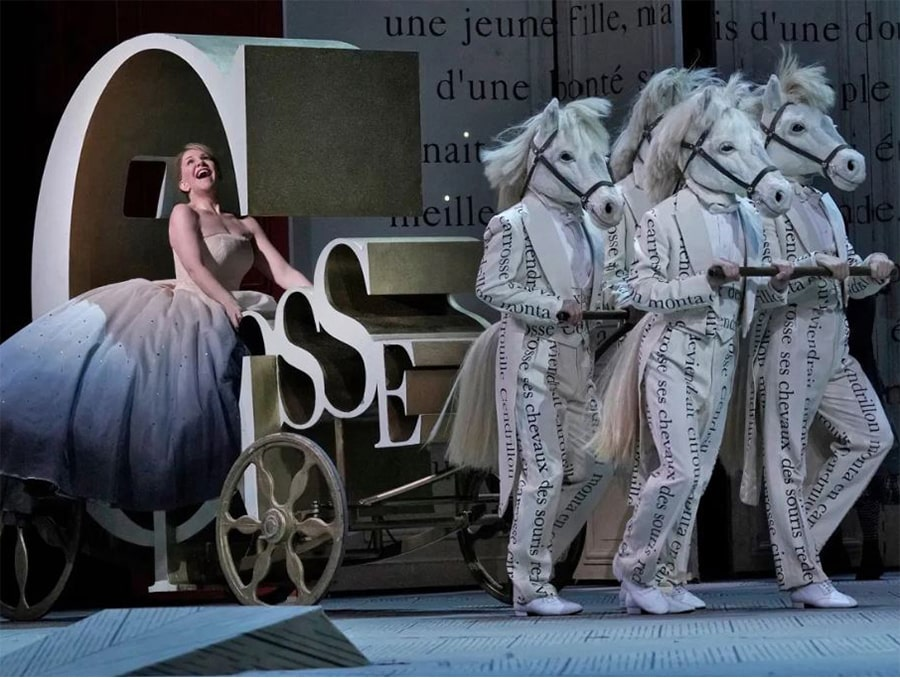 An image from the opera Cendrillon by Massenet. Cinderella is being pulled by men in white suits wearing horse masks.