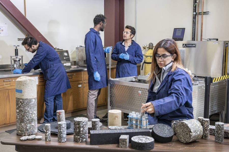 Grad students, three men and one woman, in blue lab coats work in a lab surrounded by pavement samples and related materials.