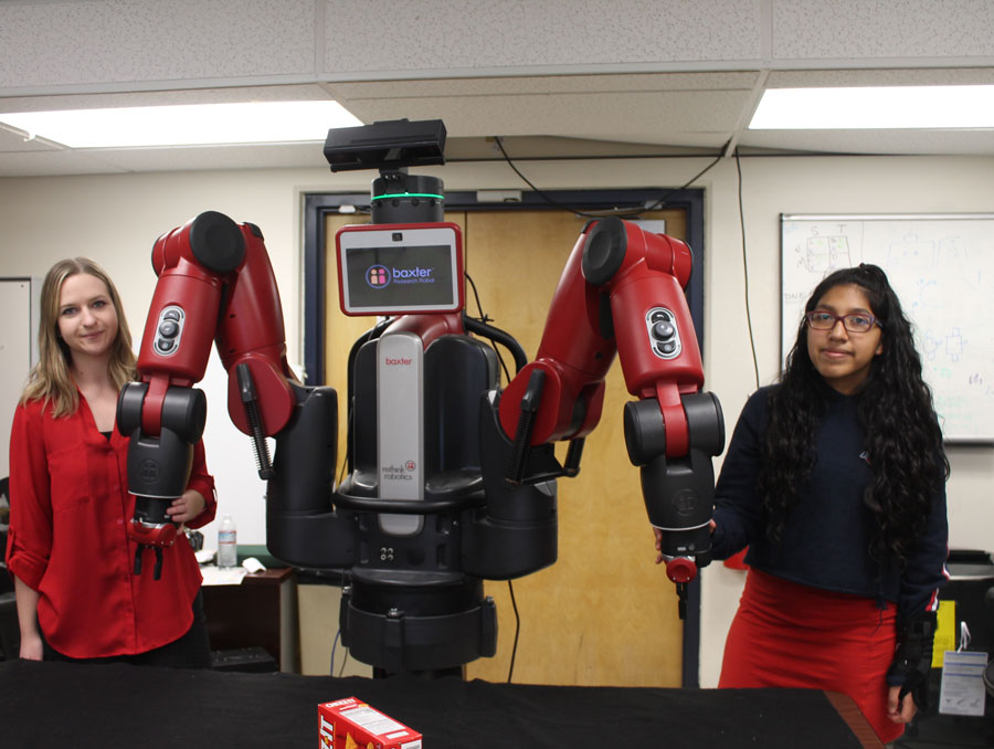 Two students pose with a robot in the lab.