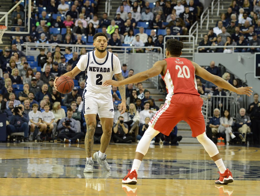 Nevada basketball guard Jalen Harris, wearing white with blue 2 on his jersey, dribbles against a UNLV opponent in red.