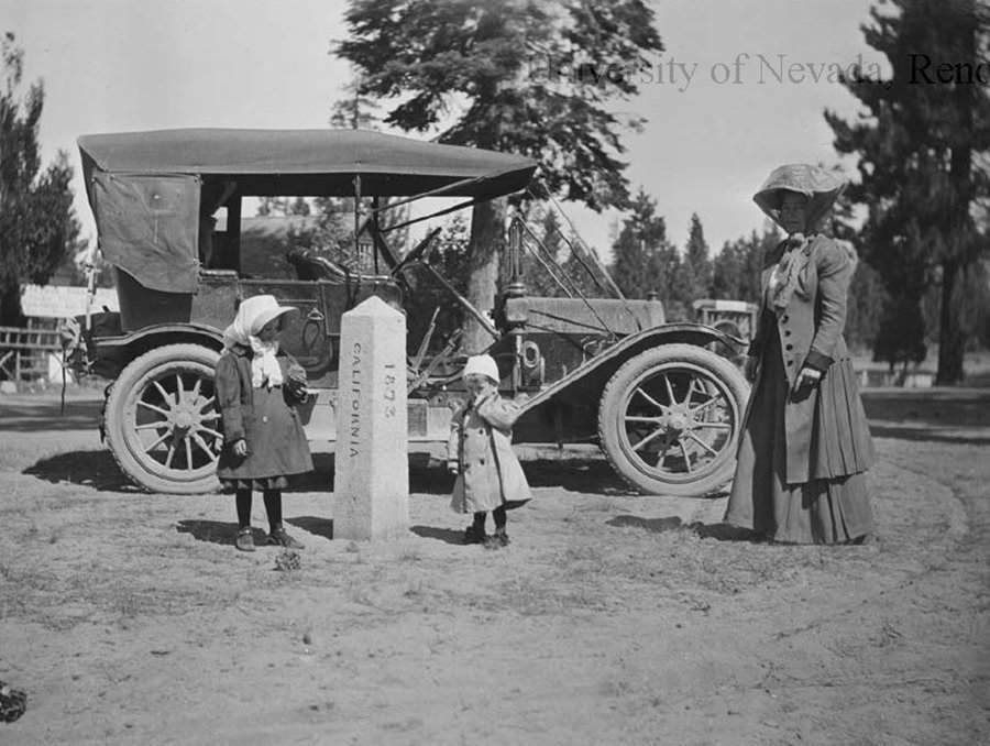 A black and white image of a woman and children next to a car