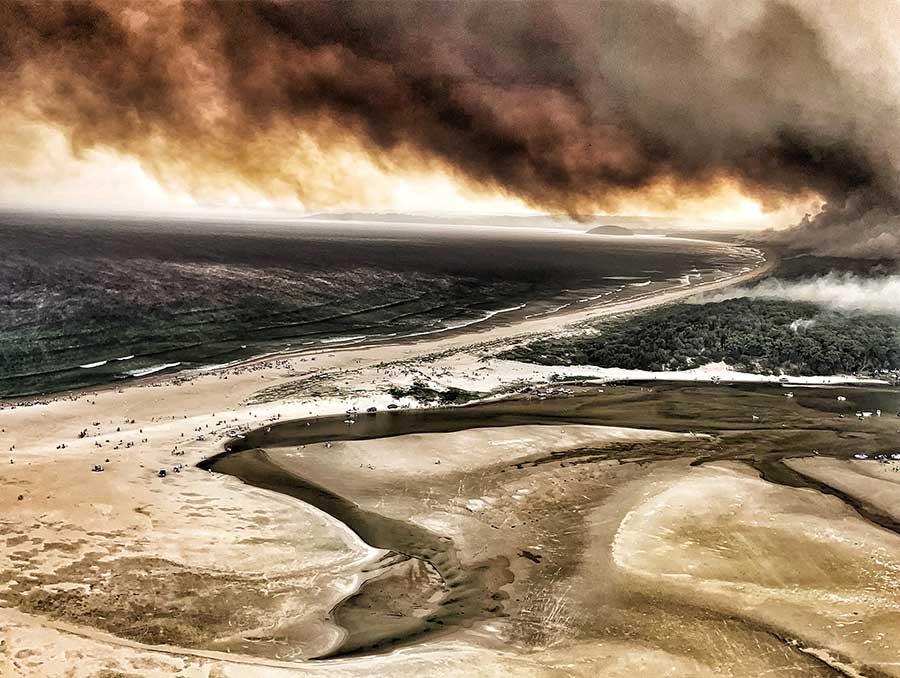 Fire raging and smoke billowing along a populated Australia coastline