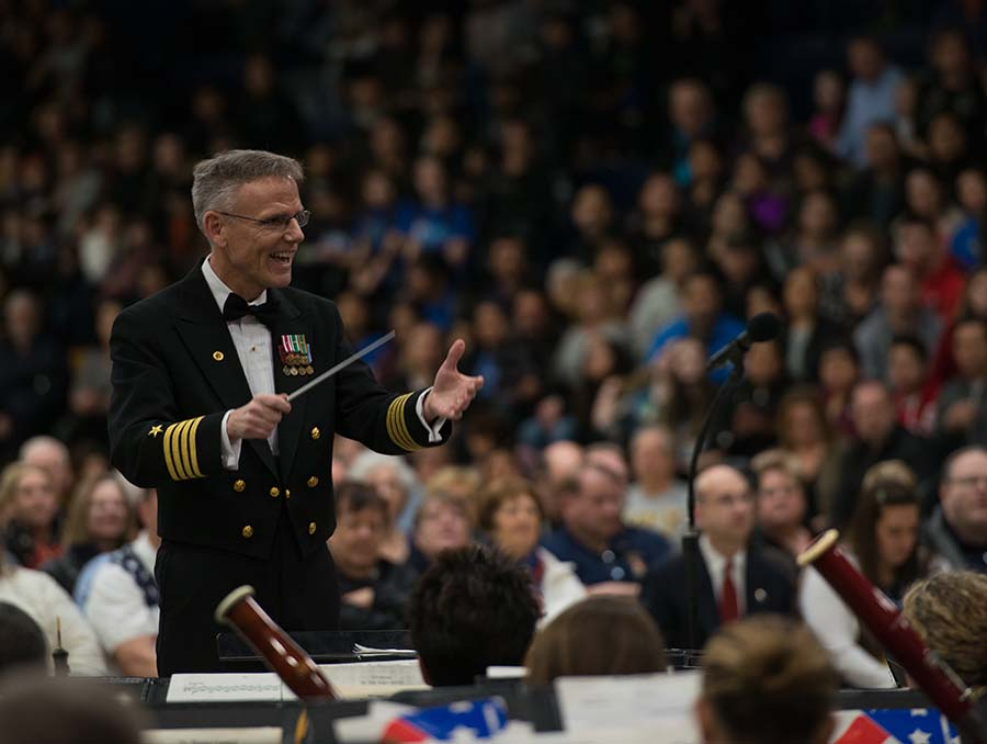 Music conductor leading the U.S. Navy Band with audience blurred behind him.
