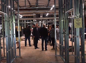 Eddy House Fundraising Event, guests are dressed nicely and standing in a framed but unfinished building