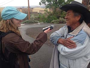 Student interviewing a day laborer while reporting for Noticiero Móvil.