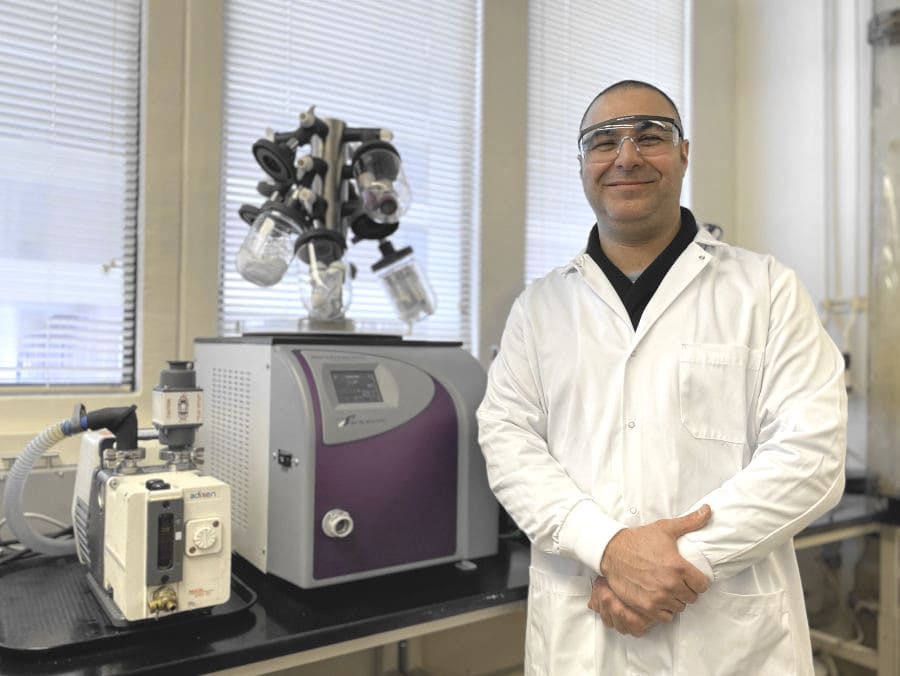 Researcher Yftah Tal-Gan in a white lab coat and safety glasses standing near lab equipment