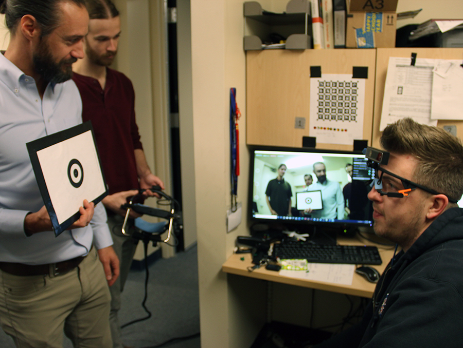 Assistant professor and students calibrate video headset