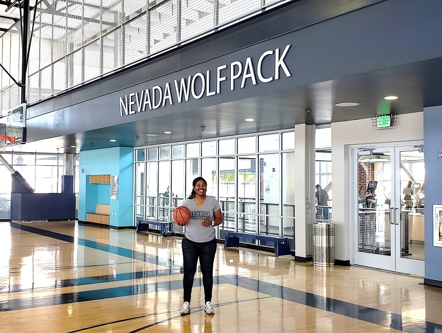Sheena Harvey holds a basketball while standing under the words Nevada Wolf Pack in the E.L. Wiegand Fitness Center