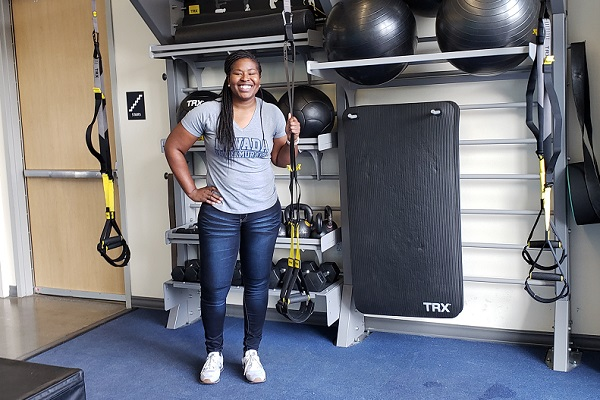 "Sheena Harvey stands in front of on of the many ""hidden gyms"" at E.L. Wiegand Fitness Center"