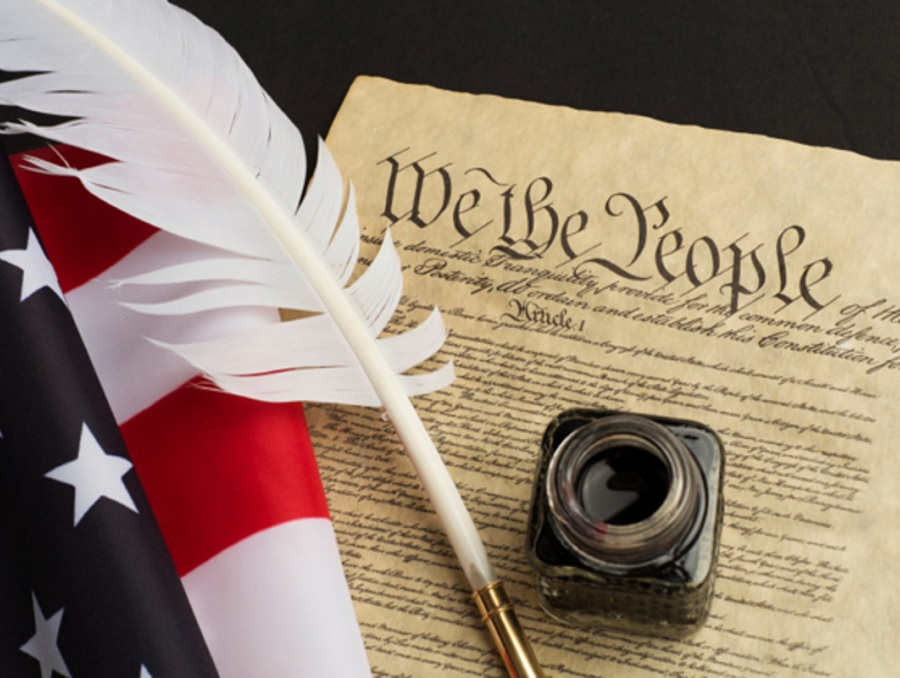 We the People document, American flag and quill pen